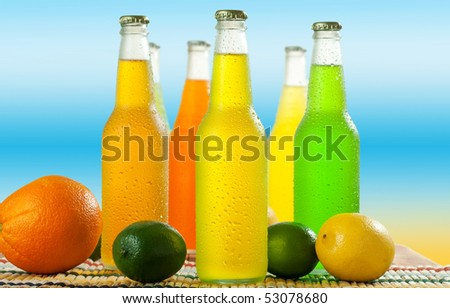 A lot of cold beverages on wooden table top and fruits next to them - stock photo