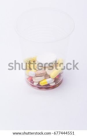 A lot of colored tablets in a plastic cup isolated on white background