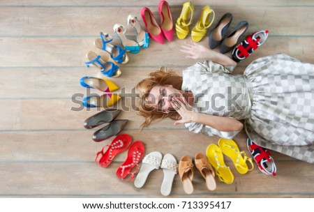 A lot of colored women's shoes on the floor. A woman chooses her shoes.
