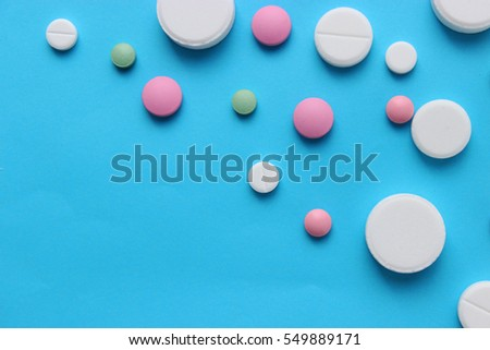 a lot of colorful pills of different shapes on a blue background. The concept of health