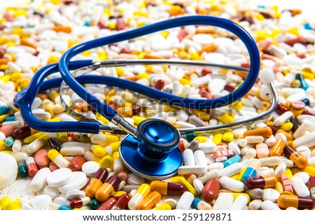 a lot of colorful pills with blue stethoscope - stock photo