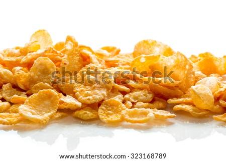 A lot of corn flakes on white ground - stock photo