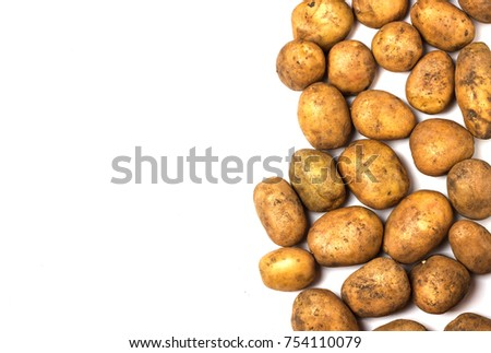 A lot of dirty potatoes on a white background. Potatoes scattered on the right side.