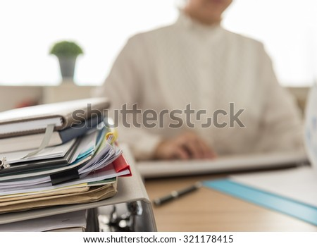 a lot of documents on desk with working women at her office. - stock photo