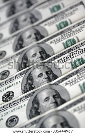 A lot of 100 dollar bank-notes with shallow depth of field. Monetization. Several hundred dollars. International currency. Money.  - stock photo