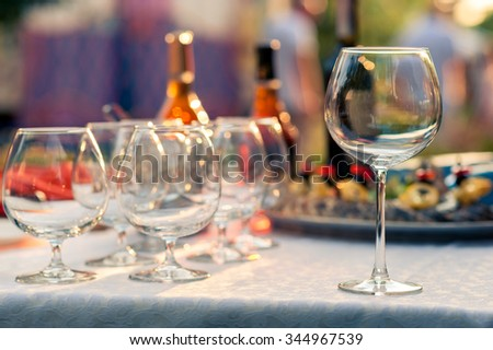 A lot of empty glasses on the table before the start of the holiday. Plate with food and bottles on a background. Close-up picture. Shallow DOF. - stock photo