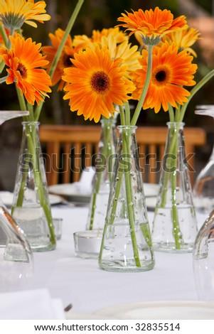 a lot of flower vase with orange gerbera - stock photo