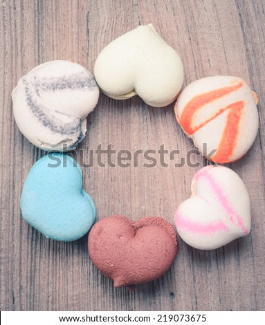 A lot of french colorful macarons in  heart shape on a woody floor in vintage tone style - stock photo