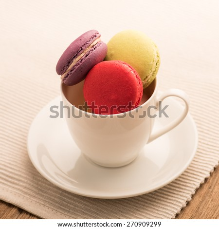 A lot of french colorful macarons on a woody floor,macarons in a cup