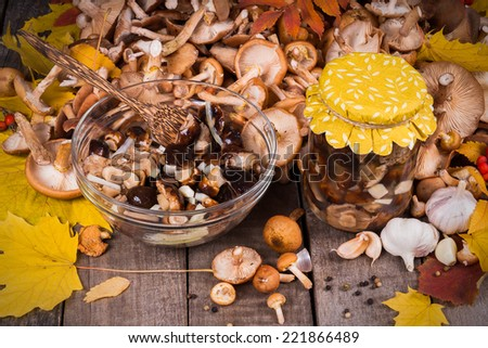 A lot of fresh and preserving  in glass jar mushrooms with spices on wooden table.