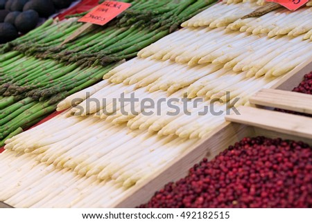 A lot of fresh asparagus on sale in food market, selective focus and nobody