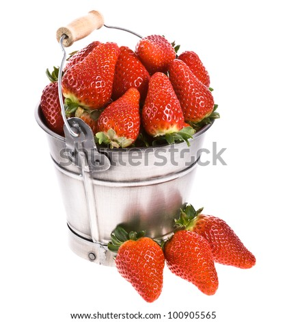 A lot of fresh strawberries and a pail . Isolated on a white background.