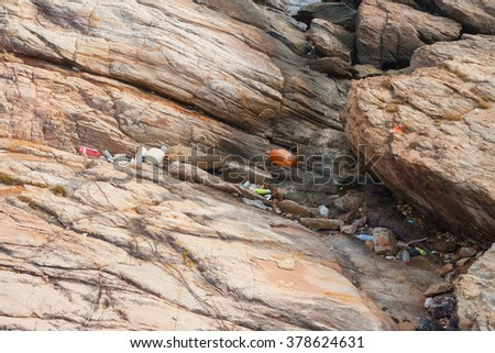 A lot of garbage on beach rock