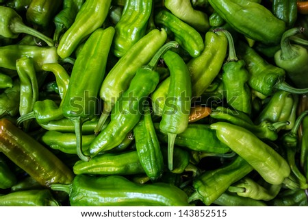 a lot of green bell peppers in a grocery store - stock photo