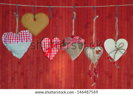 A lot of hearts on red wooden background