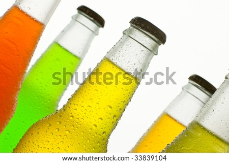 A lot of ice cold bottles with fresh tropical drinks - stock photo