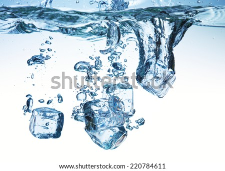 A lot of ice cubes on white background poured in water - stock photo