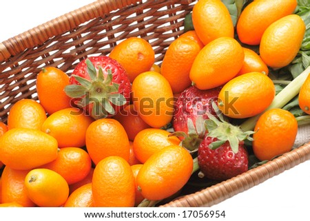 A lot of kumquats and strawberry in a basket