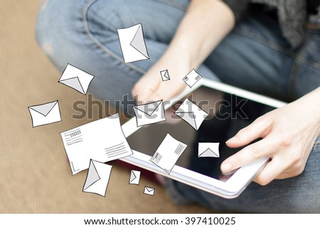 a lot of letters flying on the background of the mobile tablet in hands/receiving and sending mail - stock photo