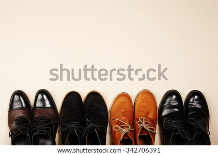 a lot of men's shoes.fashion still life men boots on old paper background.your text here - stock photo