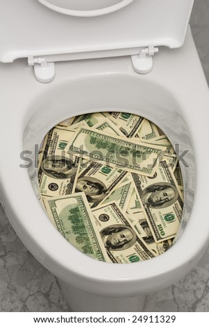 A lot of money is flushed down the toilet. - stock photo