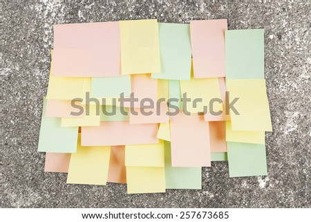 A lot of note papers on old wall - stock photo