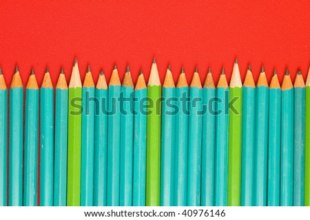 A lot of pencils in line on red backgrounds