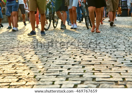 a lot of people walking on a city street. blurred legs and cobbles