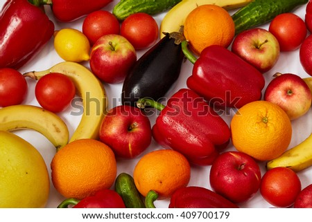 A lot of ripe vegetables and ripe fruit are spread out on a white background - stock photo