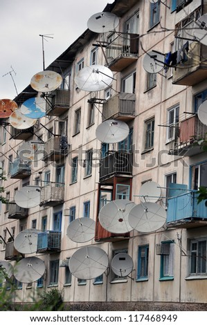 A lot of satellite dishes on the wall. - stock photo