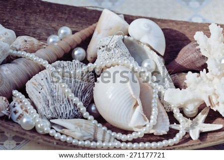 a lot of sea shells and perls in art mess close up - stock photo