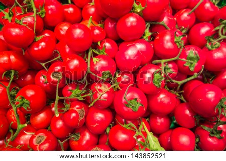 a lot of small and fresh tomatoes in a grocery store