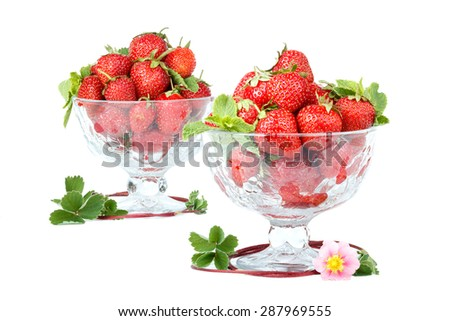 A lot of strawberries in two glass bowls over white. - stock photo