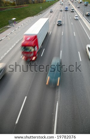 A lot of trucks and cars move on road - stock photo