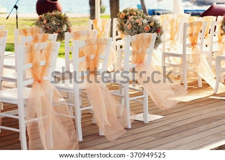 A lot of wedding chairs and luxurious tent near the pgreen lawn - stock photo