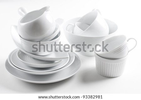 A lot of white crockery and kitchen utensils on white background - stock photo