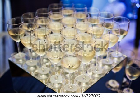 A lot of wine glasses with white tasty wine or champagne on the table at the ceremony. Glasses with alcoholic drinks. - stock photo