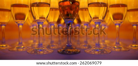 A lot of wineglasses with champagne standing at the colorful background. Yellow, red and blue colors - stock photo