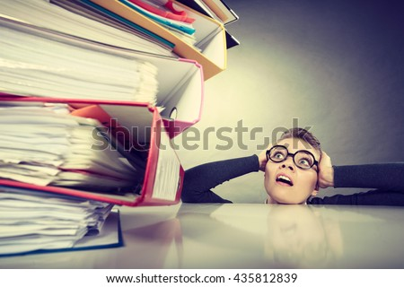 A lot of work and overwork concept. Terrified young businesswoman secretary with huge stack of binders. Scared accountant surrounded of to much work to do.