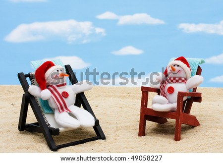 A lounge chair with snowmen on a sky background, Relaxing on your winter vacation - stock photo