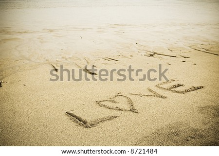 "A ""LOVE"" letter drawn on a sandy beach"