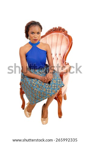 A lovely African American woman in a colorful skirt and blue blouse sitting