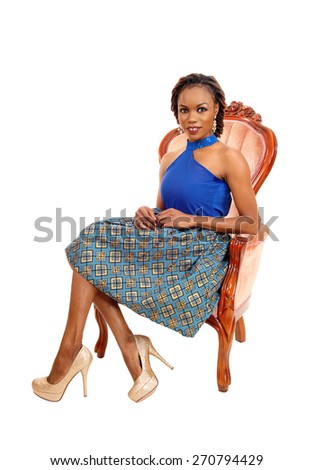 A lovely African American woman in a colorful skirt and blue blouse sitting in a pink armchair, isolated for white background.  - stock photo