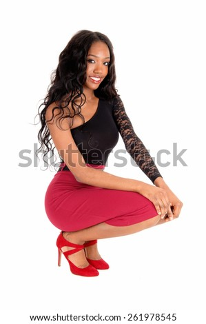 A lovely African American woman in a red skirt and black blouse crouching
