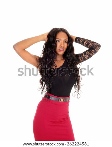 A lovely African American woman in a red skirt and black blouse standingin the studio, isolated for white background. - stock photo