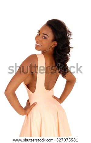 A lovely African Amerikan woman in a beige dress with long curly blackhair, looking over her shoulder, isolated for white background. - stock photo