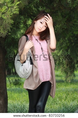 A lovely asian woman in a park' grassplot.
