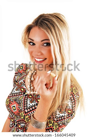 A lovely blond young woman in a colorful top holding a vitamin pill in her hand, for white background.  - stock photo