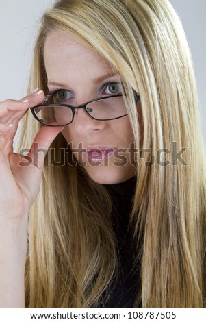 A lovely blonde nearsighted girl lowers her glasses to see clearly something in the distance.