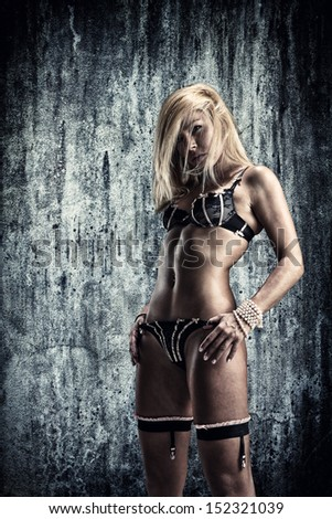 A lovely blonde woman wearing sexy lingerie in a long-abandoned warehouse facility. - stock photo